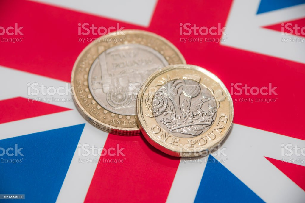 One and Two Pound coins on UK flag stock photo