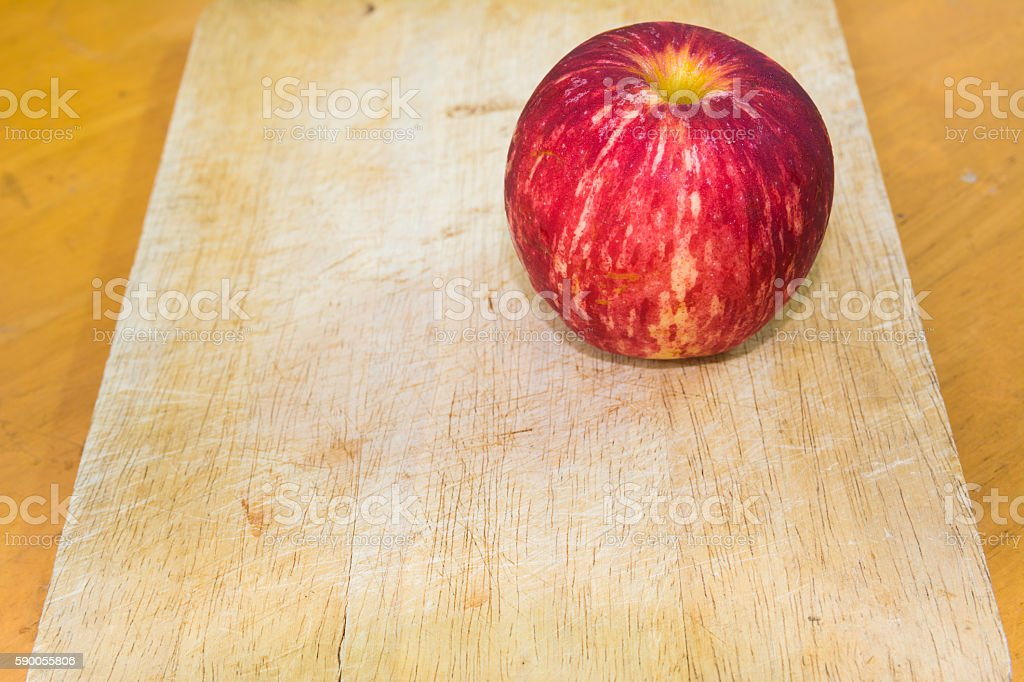 One apple on the chopping block in kitchen stock photo