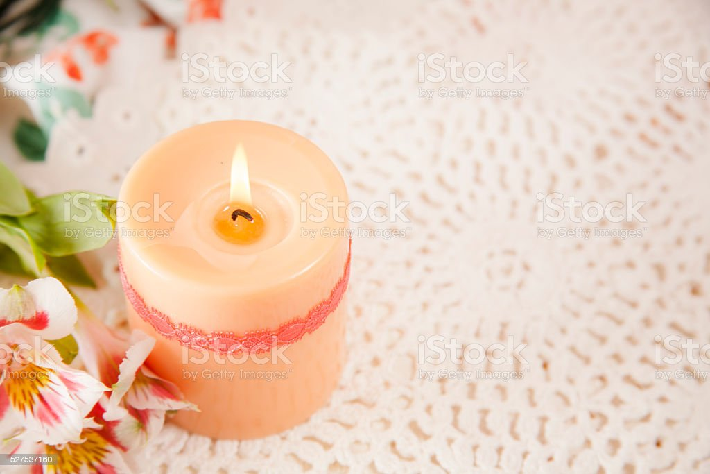 One apricot-colored burning candle with copyspace. Flowers. stock photo