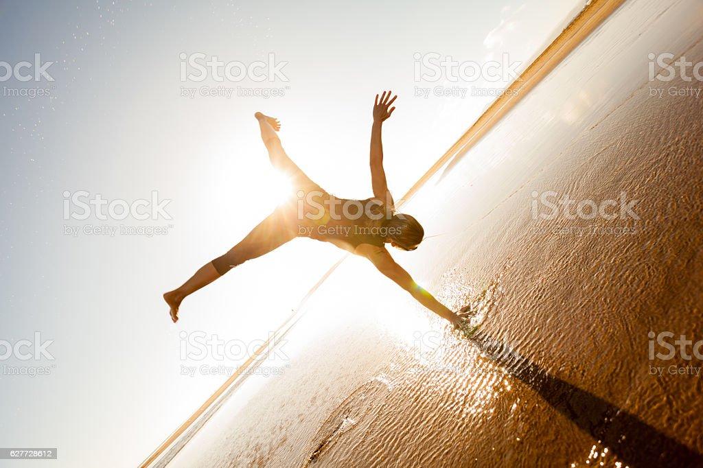 one armed cartwheel on wet beach stock photo