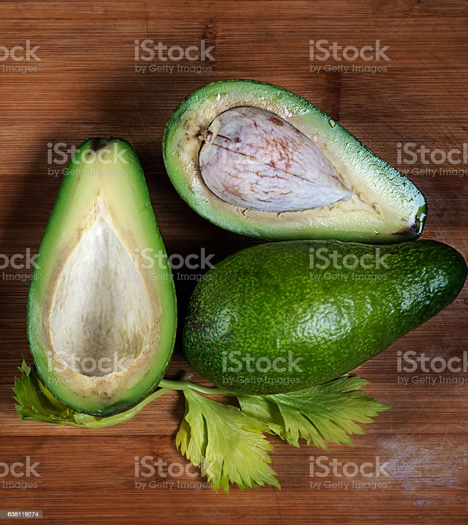 One avocado cut in half on a wooden surface   shows stock photo