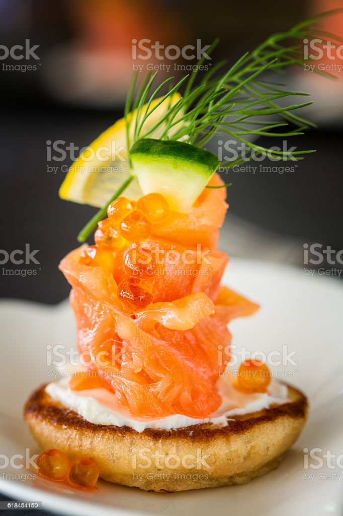 One Blini appetizer with smoked salmon and sour cream stock photo