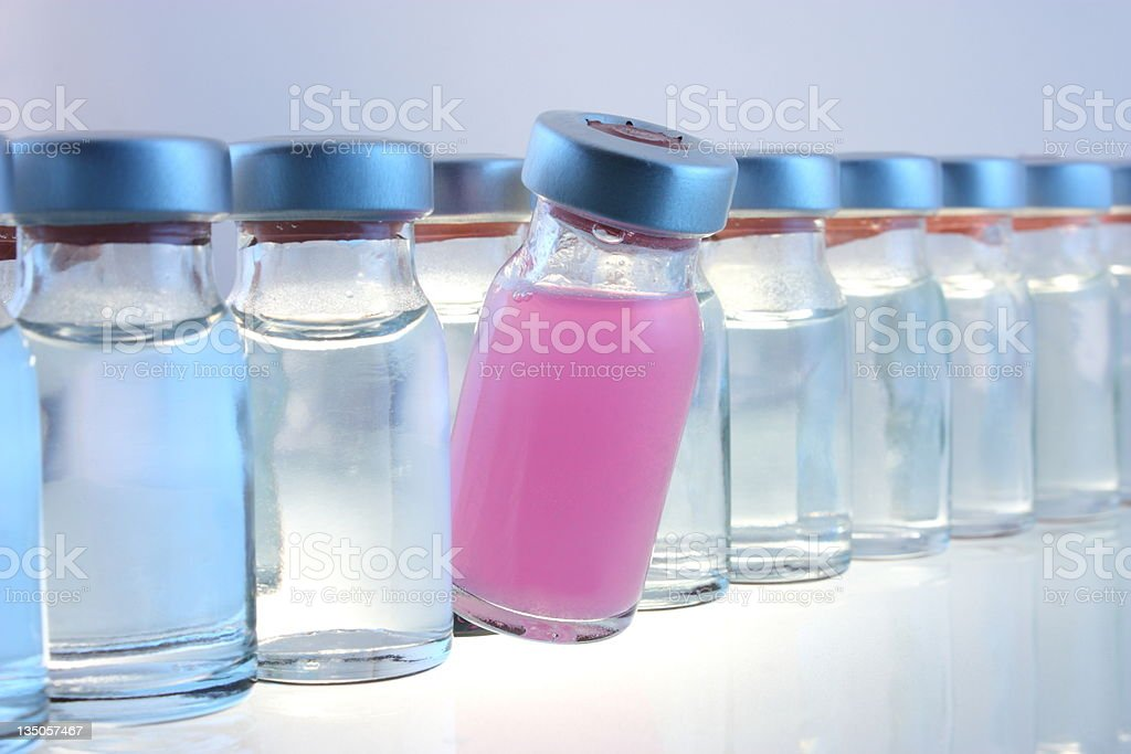 One bottle of pink liquid in a line of several bottles stock photo