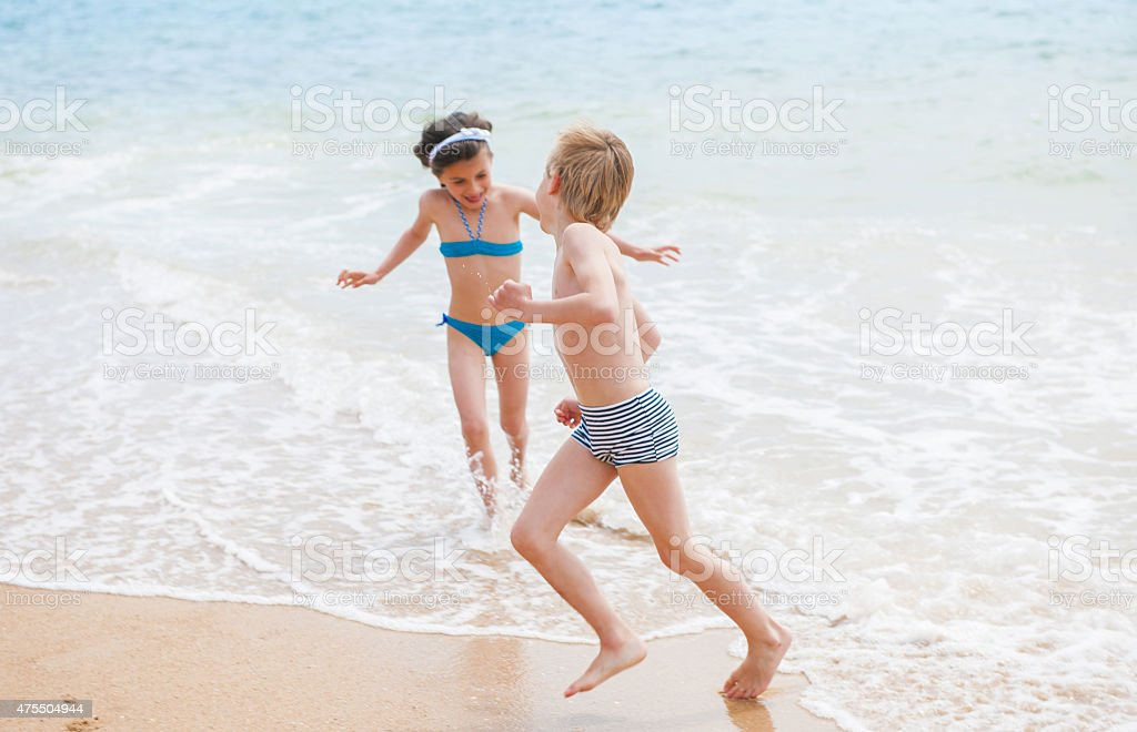 one boy and one girl are playing in the waves stock photo