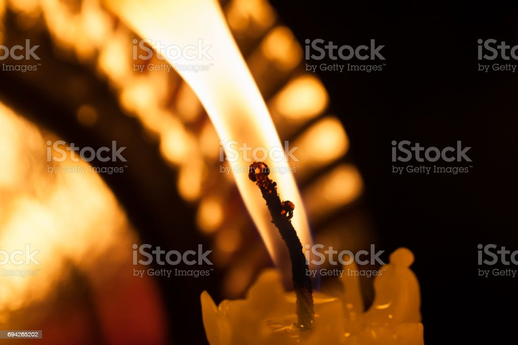 One burning candle in the dark stock photo