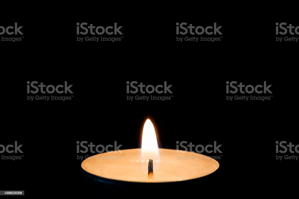 One burning tealight in darkness, closeup stock photo