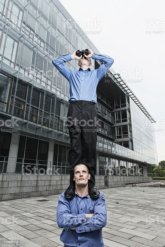 One businessman with binoculars stands on the shoulder of coworker royalty-free stock photo