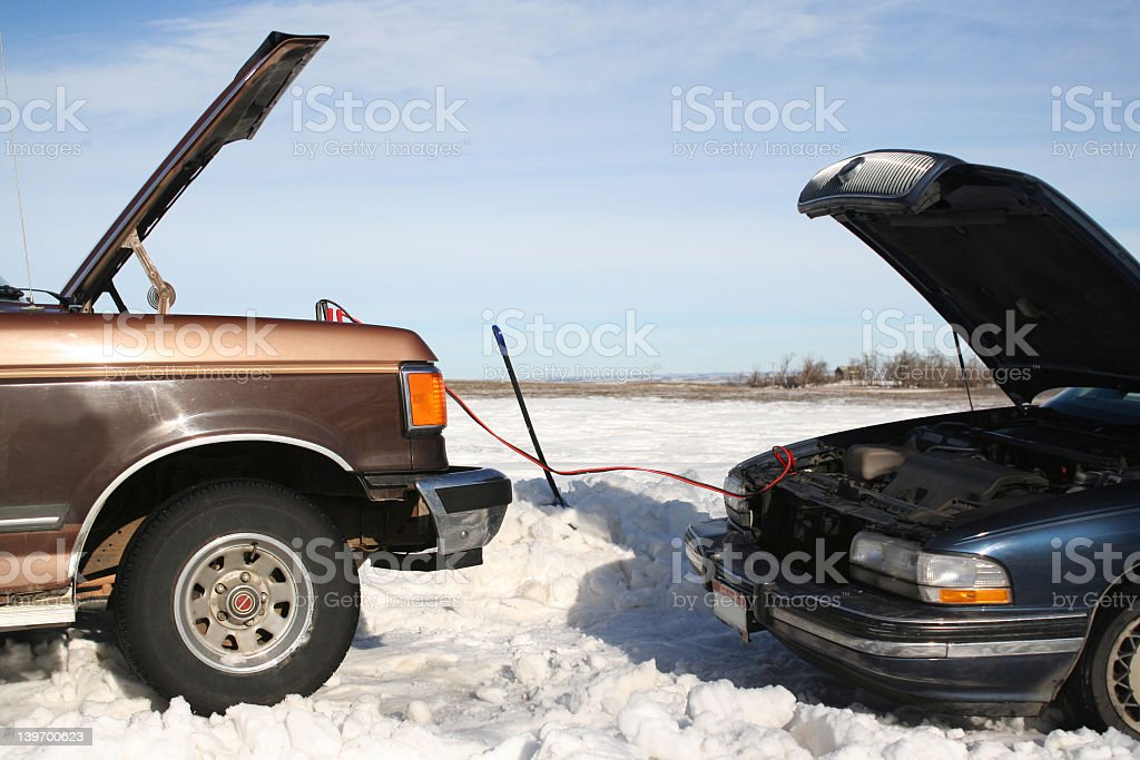 One car helping another to jump start in winter  stock photo
