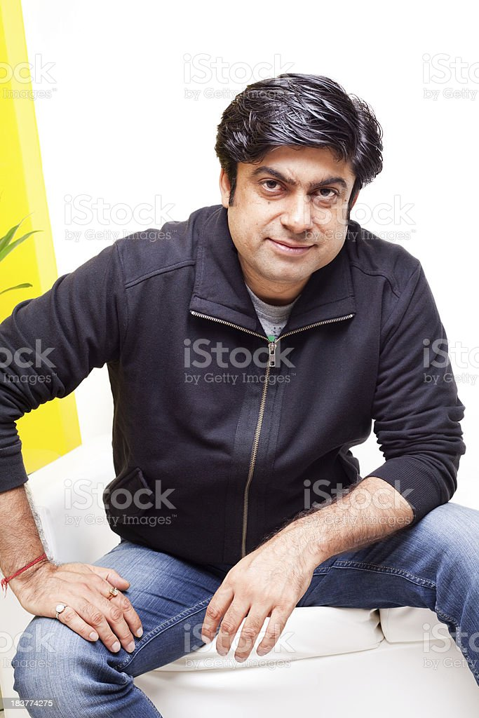 One Casual Asian Indian Man sitting on White Couch Sofa royalty-free stock photo