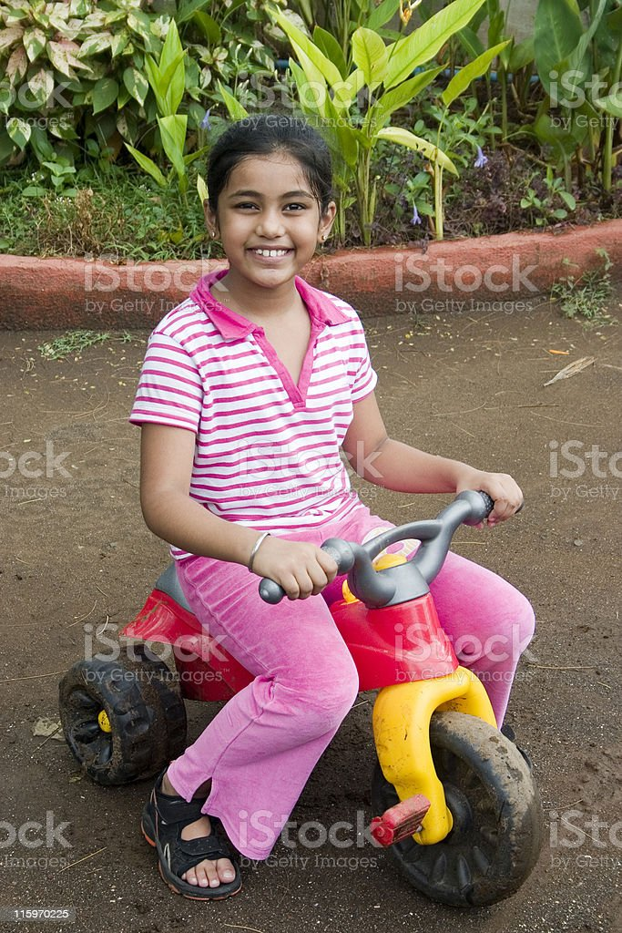 One Cheerful Indian Asian Child Girl People Vertical riding Tri-Cycle royalty-free stock photo
