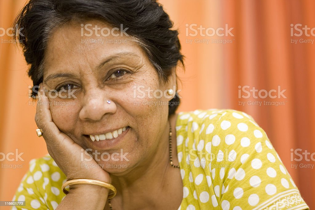 One Cheerful Indian Senior Lady female horizontal hand on chin royalty-free stock photo