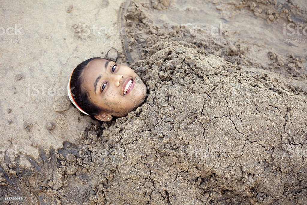 One Cheerful Little Indian Girl Buried Covered in Beach Sand royalty-free stock photo