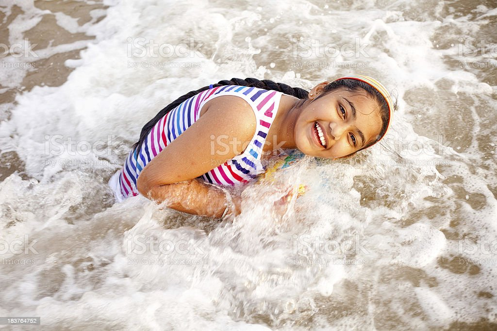 One Cheerful Little Indian Girl Playing Enjoying on Beach Waves royalty-free stock photo