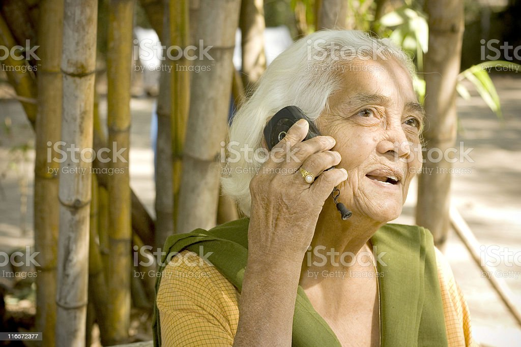 One cheerful senior Asian Indian woman female on the phone royalty-free stock photo