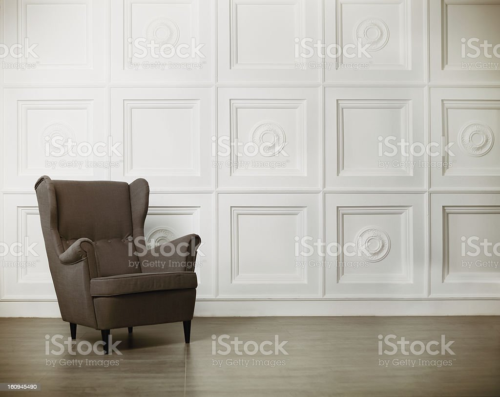One classic armchair against a white wall and floor stock photo