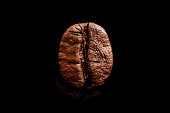 One coffee bean isolated on pure black background.