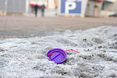 One compressed plastic bottle isolated. Waste in cityscape