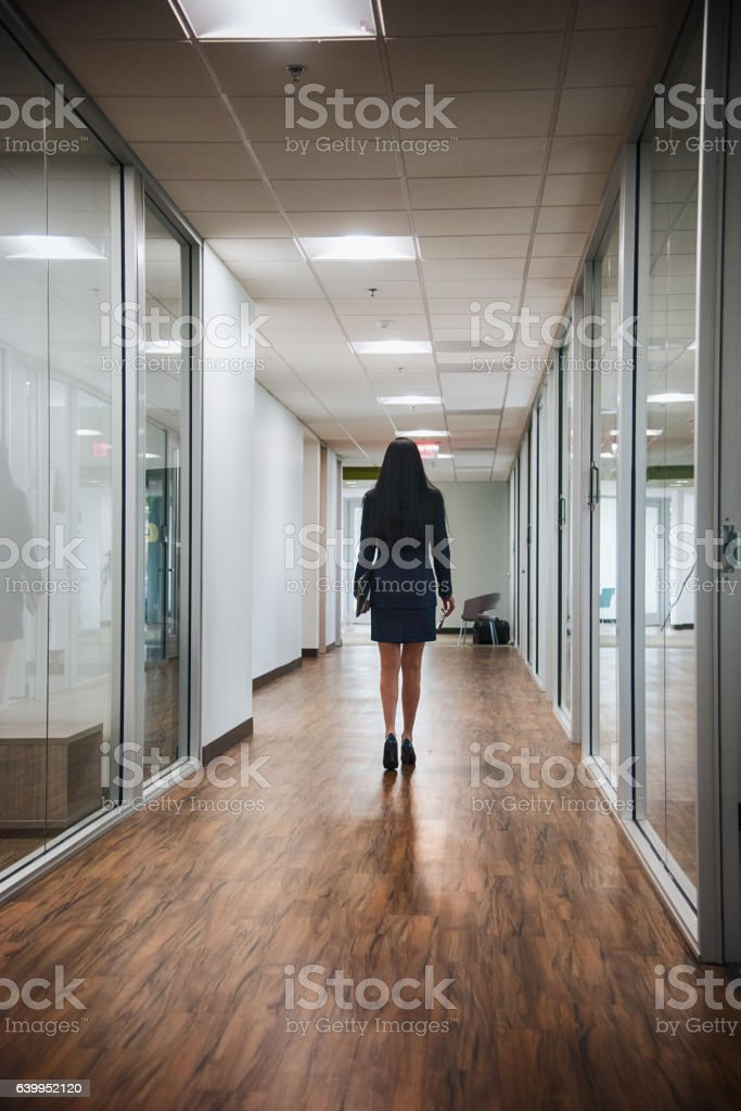 One Confident Businesswoman Walking Alone Through the Office stock photo