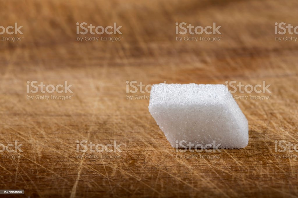 One cube of sugar on wood stock photo