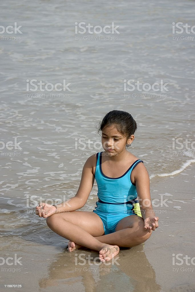 One Cute Indian Girl Kid Beach doing Yoga Vertical Water royalty-free stock photo