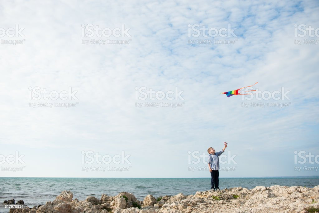 one cute small boy holding a kite flying in the sky on the background of ocean stock photo