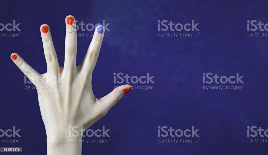 One different nail color in finger in caucasian hand. Red and blue painted fingernails. Dare to be different, originality and creativity concept with blue background. Stand out from the crowd. stock photo