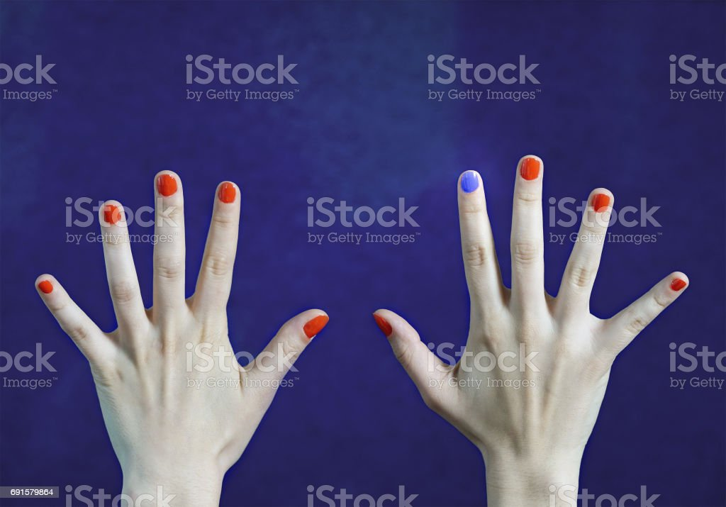 One different nail color in finger in caucasian hands. Red and blue painted fingernails. Stand out from the crowd, originality and creativity concept with blue background. Dare to be different. stock photo