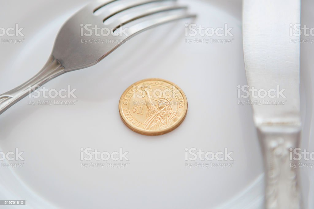 One dollar coin on a white plate stock photo