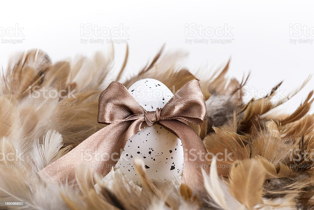 One Easter egg, ribbon, stones and feathers royalty-free stock photo