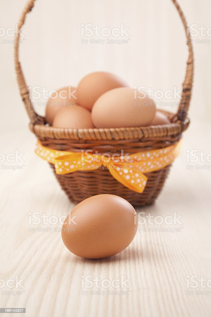 one egg in front of little basket with yellow bow royalty-free stock photo