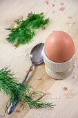 One egg in the wooden pot with spoon and dill