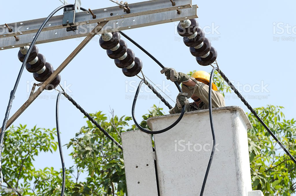 One electrician repairing electric power system from lift bucket. stock photo