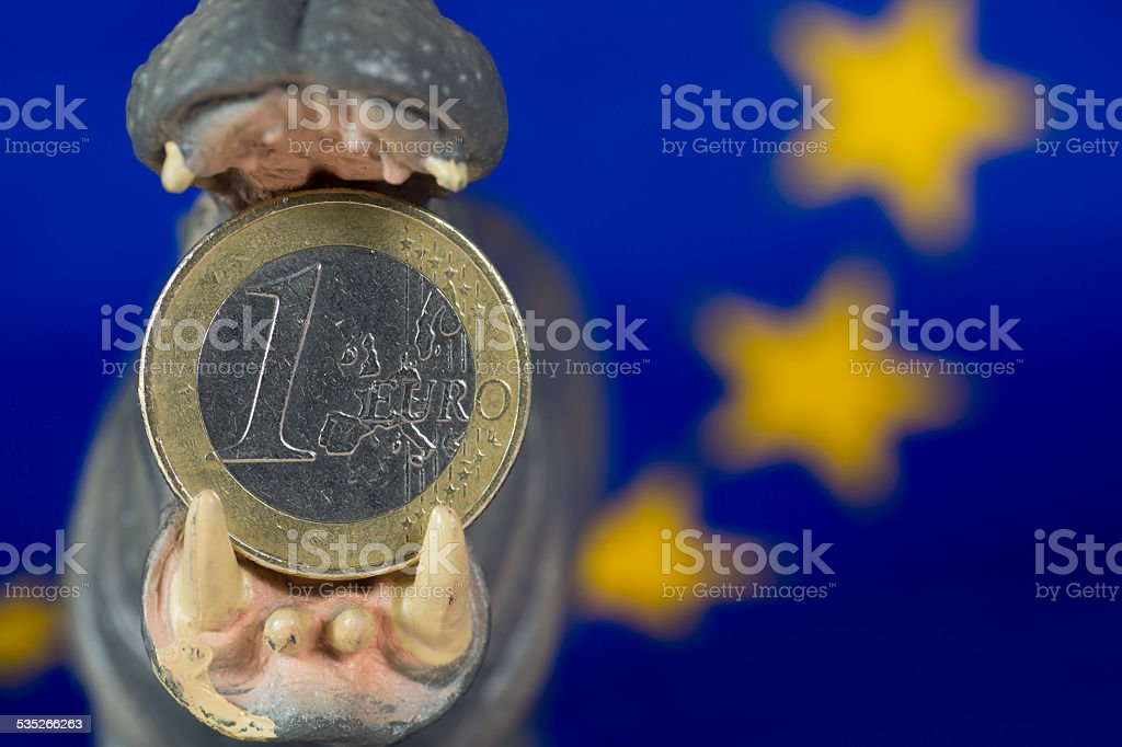 One Euro coin in mouth of hippo figurine stock photo