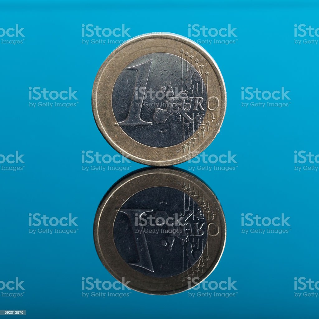 One Euro money coin on blue with reflection stock photo