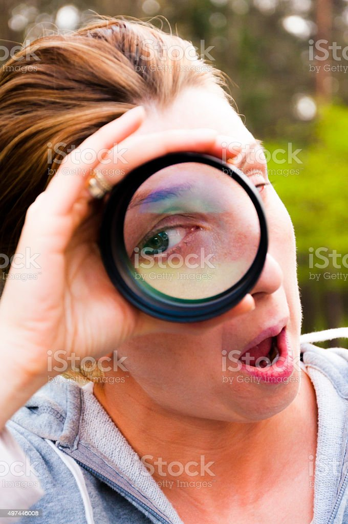One eye watching woman through magnifying lens stock photo
