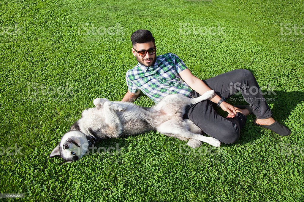One fashion middle eastern is resting, enjoy with his dog. stock photo