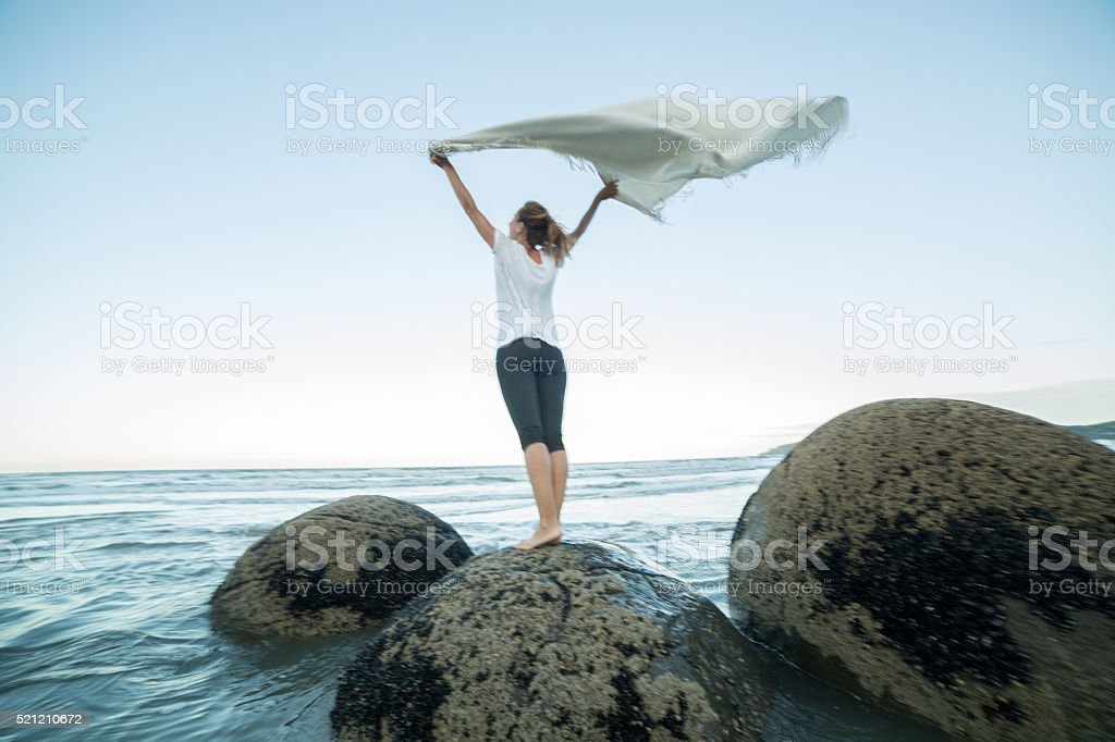 One female stands on boulder, holds blanket in the air stock photo