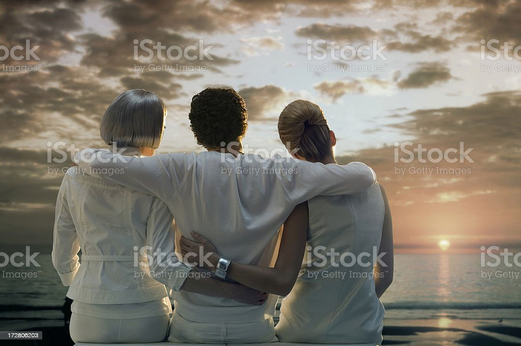 One futuristic man and two women watching the sunset royalty-free stock photo