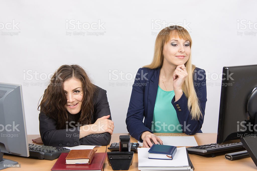 one girl crazy looks picture, her colleague looking at monitor stock photo