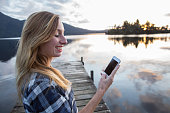 One girl on lake pier text messaging on mobile phone