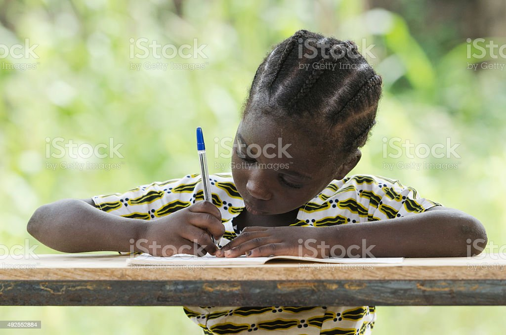 young black child writing down some notes during class outdoors....
