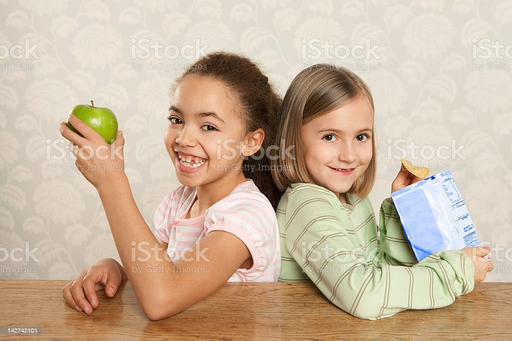 One girl with an apple, one girl with a packet of crisps stock photo