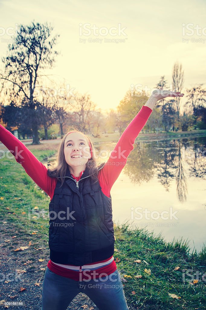 One girl with hands up against sunset royalty-free stock photo