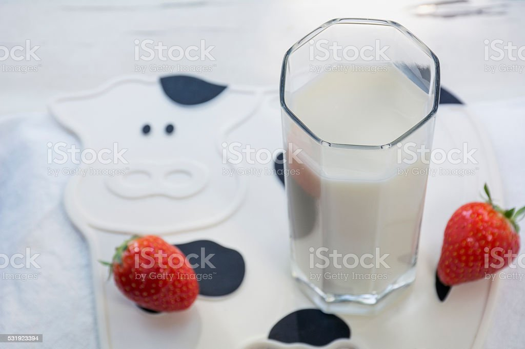 One glass of milk with several strawberries on the mat stock photo
