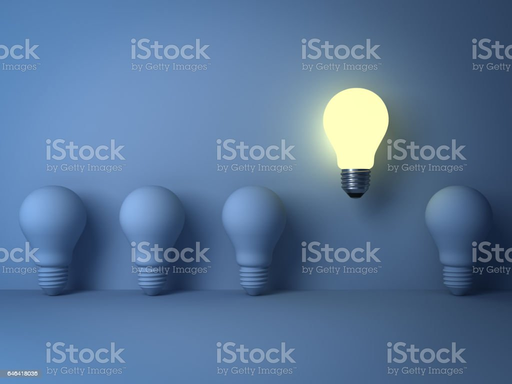 One glowing light bulb standing out from the unlit incandescent bulbs on blue background with shadow , The business concept and individuality concept stock photo