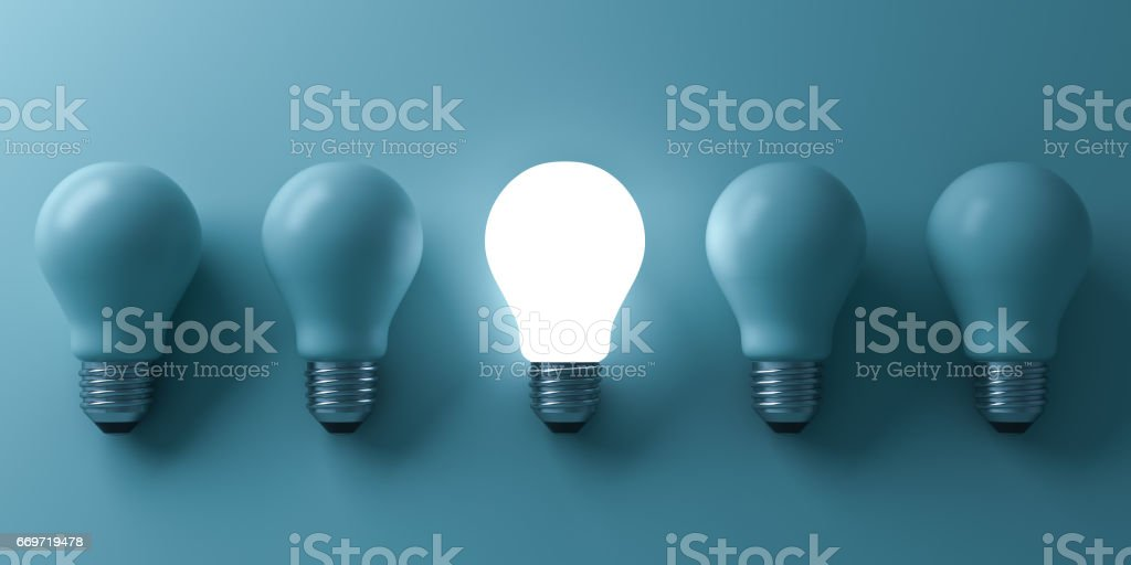 One glowing light bulb standing out from the unlit incandescent bulbs on green background with reflection and shadow , individuality and different business creative idea concepts . 3D rendering stock photo