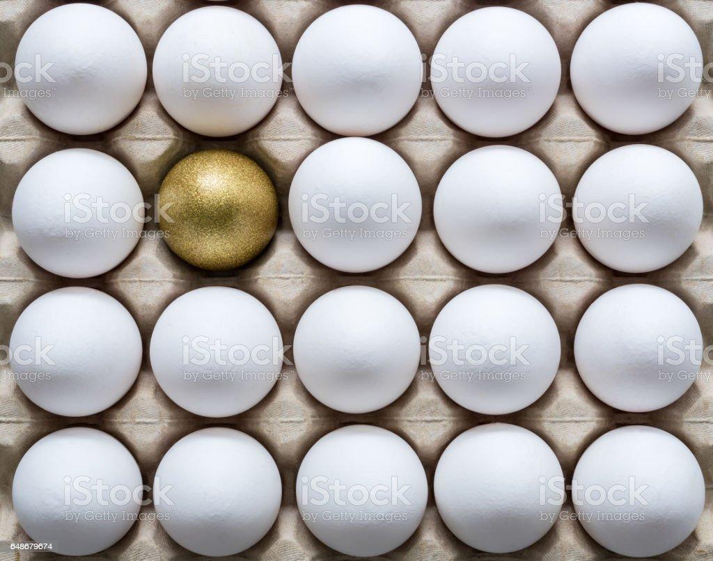 One golden egg among white eggs in a carton egg box stock photo
