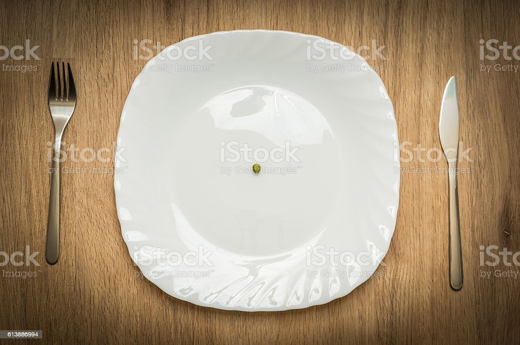 One green pea on white plate stock photo