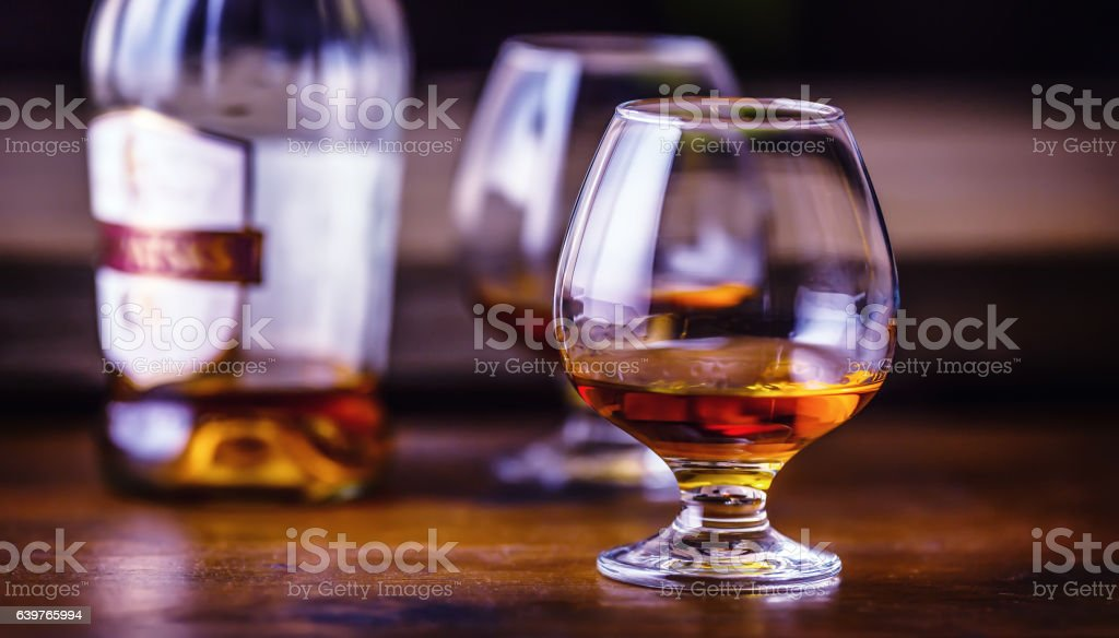 One half full glasses of cognac on a wooden surface. stock photo