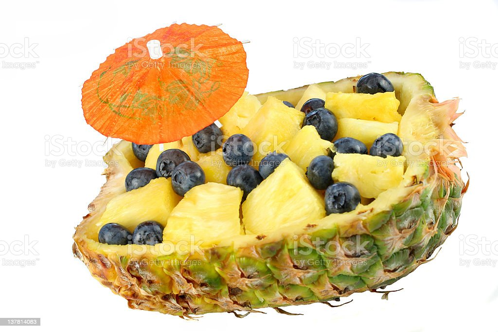 One half of pineapple filled with cubes and blueberries royalty-free stock photo